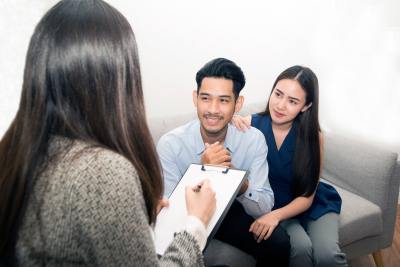 asian couple sitting on couch talking to therapist in therapist's office